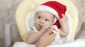 La maman alimente le bébé dans le chapeau rouge de Santa de la petite cuillère se reposant dans le siège d'enfant Noël An neuf Pl banque de vidéos