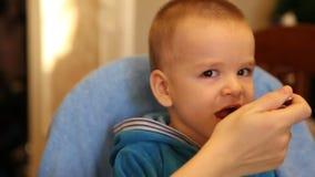 La maman alimente le gruau de bébé d'une cuillère banque de vidéos