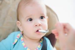 La maman alimente ses neuf mois de bébé à la maison Photographie stock
