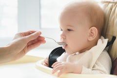 La maman alimente ses neuf mois de bébé à la maison Photos libres de droits