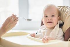 La maman alimente ses neuf mois de bébé à la maison Photos stock