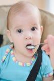 La maman alimente ses neuf mois de bébé à la maison Photo stock