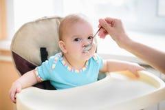 La maman alimente ses neuf mois de bébé à la maison Image libre de droits