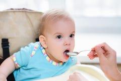 La maman alimente ses neuf mois de bébé à la maison Photographie stock libre de droits