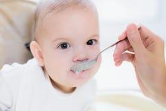 La maman alimente ses neuf mois de bébé à la maison Images stock
