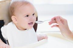 La maman alimente ses neuf mois de bébé à la maison Photo libre de droits