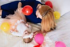 La maman amuse son enfant et montre une boule rouge bien aérée la fille avec ses yeux le regarde Photographie stock libre de droits