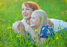 La maman avec des accolades et sa petite fille se trouvent dessus Photos libres de droits