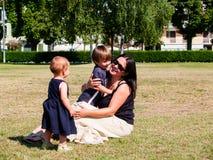 La maman avec ses deux enfants en bas âge s'assied dans un pré Photographie stock