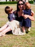 La maman avec ses deux enfants en bas âge s'assied dans un pré Photos libres de droits