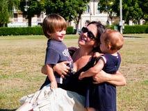 La maman avec ses deux enfants en bas âge s'assied dans un pré Images libres de droits