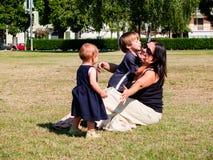 La maman avec ses deux enfants en bas âge s'assied dans un pré Photos stock