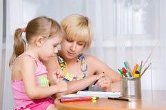 La maman avec un enfant dessine Photographie stock