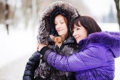 La maman avec une fille et leur chien marchant en hiver se garent Image libre de droits
