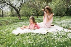 La maman avec une petite fille a lu des livres Photos stock
