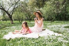 La maman avec une petite fille a lu des livres Images stock