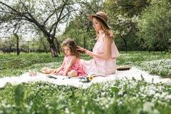 La maman avec une petite fille a lu des livres Image stock
