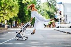 La maman avec une poussette traverse la route photographie stock libre de droits