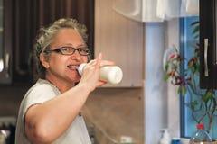 La maman boit du lait d'un biberon images libres de droits