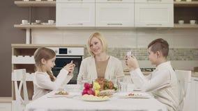 La maman communique avec ses enfants à la table pendant un dîner de famille clips vidéos