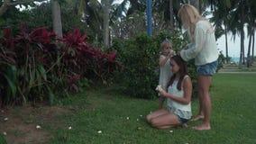 La maman décore des cheveux du ` s de fille avec des fleurs de vidéo de longueur d'actions de Plumeria banque de vidéos