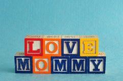 La maman d'amour de mots a orthographié avec des blocs d'alphabet contre un bleu Photo libre de droits