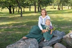 La maman de famille avec la fille en rétro toile de vintage habille se reposer sur une roche en pierre dans la forêt de parc avec Photo stock