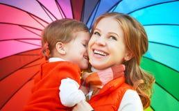 La maman de famille et la fille heureuses d'enfant avec l'arc-en-ciel ont coloré l'umbrell Image libre de droits