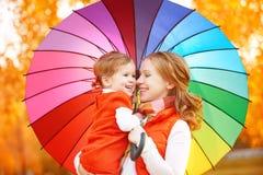 La maman de famille et la fille heureuses d'enfant avec l'arc-en-ciel ont coloré l'umbrell Photos libres de droits