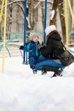 La maman donne à fils par tasse de thé sur le terrain de jeu Promenade d'hiver pendant l'après-midi Photographie stock