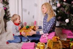 La maman donne un petit cadeau de Noël d'enfant Photos stock