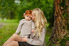La maman embrasse doucement le bébé roux sur le backg de forêt d'automne Photographie stock libre de droits