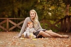 La maman embrasse doucement le bébé roux sur le backg de forêt d'automne Image libre de droits
