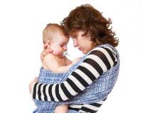 La maman embrasse son petit bébé triste image stock