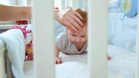 La maman en gros plan joue avec un petit enfant en bas âge dans la huche riant la vue de côté par le treillis de la huche Enfance banque de vidéos