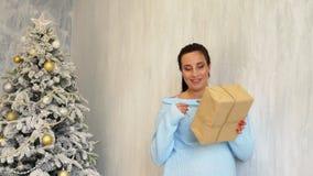 La maman enceinte se tient prêt l'arbre de Noël avec des cadeaux de Noël blanc clips vidéos