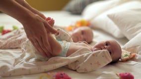 La maman enlève des vêtements de l'enfant et fait la gymnastique spéciale pour des nouveaux-nés à partir des premiers jours de la clips vidéos