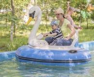 La maman enseigne à son contrôle de fils un bateau-cygne Photo libre de droits