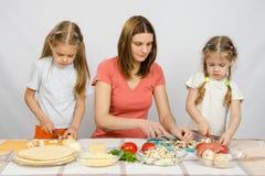 La maman enseigne deux filles à faire cuire Image libre de droits