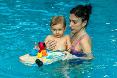 La maman enseigne le bébé à nager Photo stock