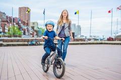 La maman enseigne le fils à monter un vélo en parc images libres de droits