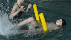 La maman enseigne le fils de sept ans à nager dans la piscine clips vidéos