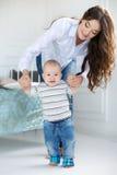 La maman enseigne le jeune fils à marcher Photographie stock