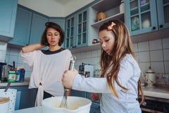 La maman enseigne sa petite fille à faire cuire la nourriture Photographie stock libre de droits