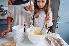 La maman enseigne sa petite fille à faire cuire la nourriture Photos libres de droits