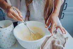 La maman enseigne sa petite fille à faire cuire la nourriture Image stock