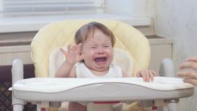 La maman essuie le visage du bébé Le bébé apprend à manger du gruau de la cuillère Le bébé est se reposer capricieux et pleurant  banque de vidéos