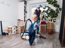 La maman et la fille dans des combinaisons bleues de denim ont nettoyé à la maison et nettoyé à l'aspirateur photographie stock