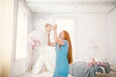 La maman et la fille de famille un an s'amusent à l'intérieur de l'intérieur La femme met les bras du ` s d'enfant et la pousse photographie stock libre de droits