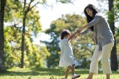 La maman et la fille en parc apprécient Photographie stock
